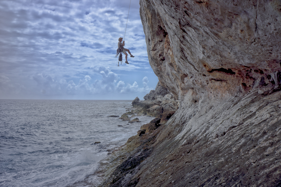Rock climbing over tropical ocean waters.